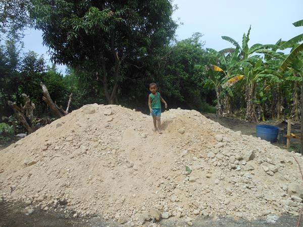 child on pile of sand