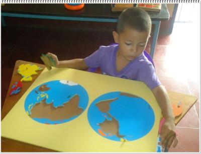 A child working with a Montessori puzzle map in Puerto Morazán